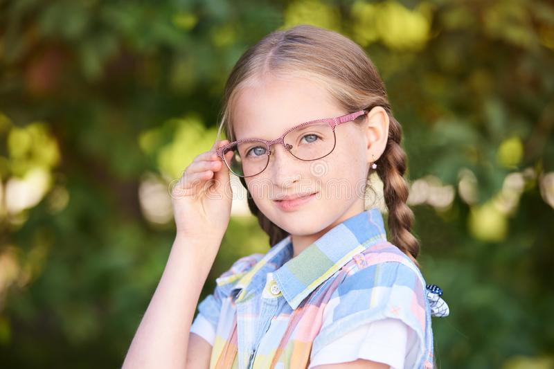 Casual schoolchildren. Little girl smile. Standind outdoor with eyeglasses. First grade royalty free stock photo
