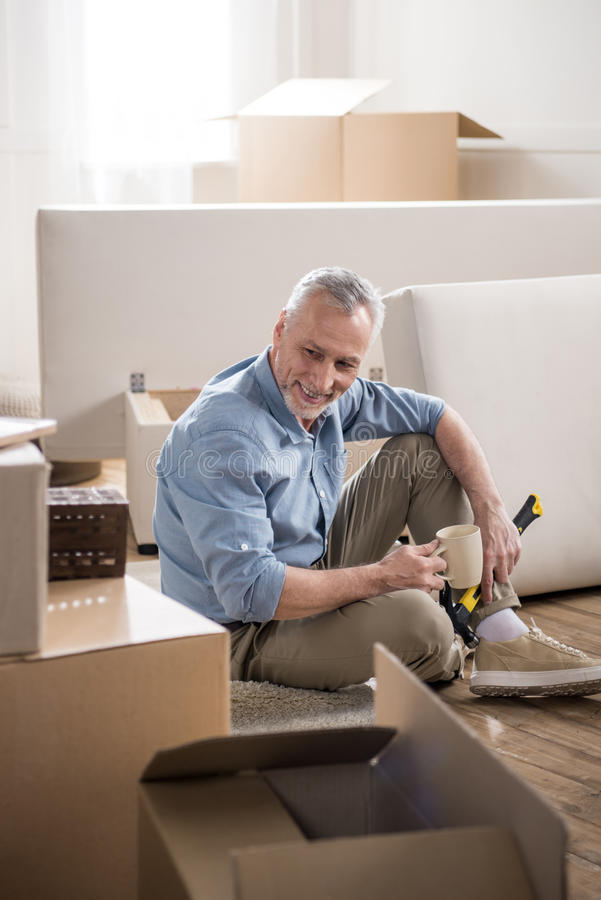 Casual senior man sitting on the floor with hammer and drinking coffee royalty free stock photo