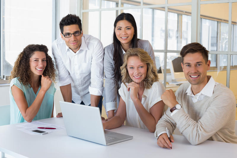 Casual smiling business team having a meeting using laptop. In the office royalty free stock photography
