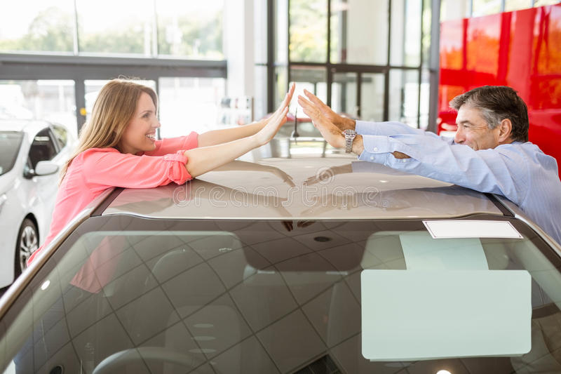 Casual smiling couple hugging their new car. At new car showroom royalty free stock photo
