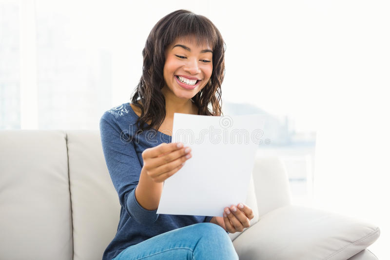 Casual smiling woman reading paper royalty free stock image