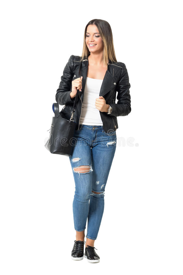 Casual street style fashion girl with handbag smiling and looking down. Full body length portrait isolated over white background royalty free stock images