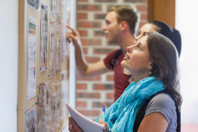 Casual students looking at notice board stock photos