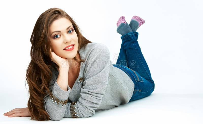Casual stule woman full body portrait. Model with long hair lying on a floor royalty free stock image