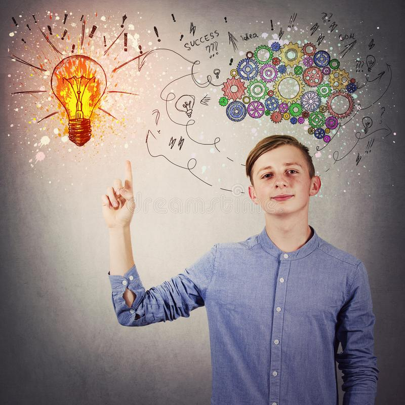 Casual teen boy pointing his index finger up showing a bright light bulb on the wall. Idea concept, positive thinking as colorful royalty free stock image
