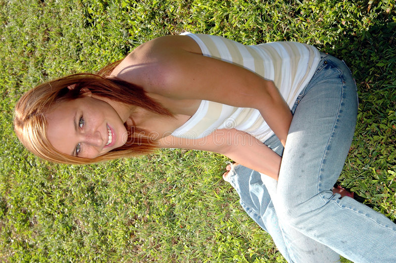 Casual teen on grass. A pretty strawberry blonde teenager sitting in the grass royalty free stock photos
