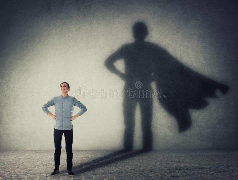 Casual teenage, keeps arms on hips smiling confident, casting a superhero with cape shadow on the wall. Student ambition success. Concept. Leadership hero power stock photo