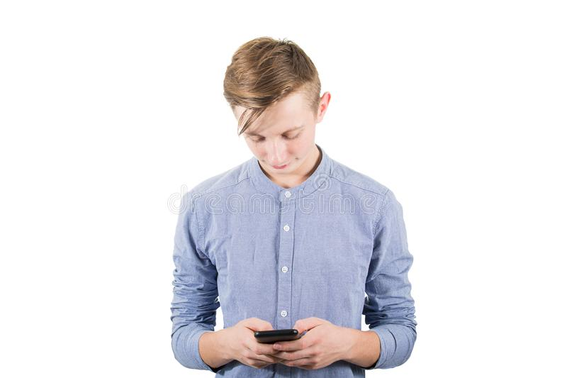 Casual teenager boy using his mobile phone to text someone isolated over white background. Adolescent guy communicate with his. Friends on social media stock photography