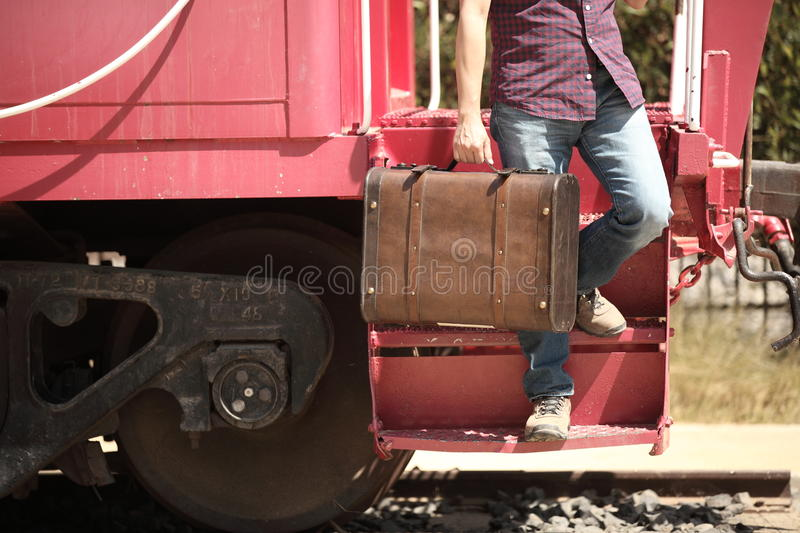 Casual tourist with a retro suitcase getting off the train. stock photos