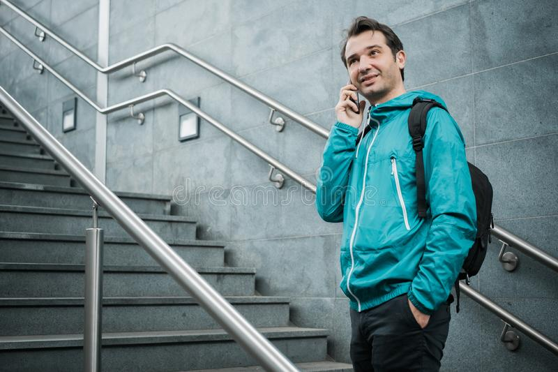 Casual urban male using smartphone on stairs. Outdoor portrait of modern young man with mobile phone royalty free stock photography