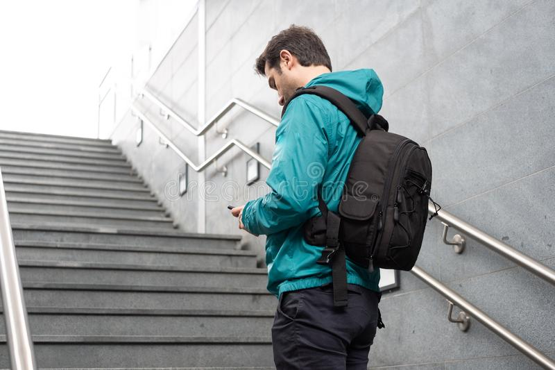 Outdoor portrait of modern young man with mobile phone. Casual urban male using smartphone on stairs royalty free stock images