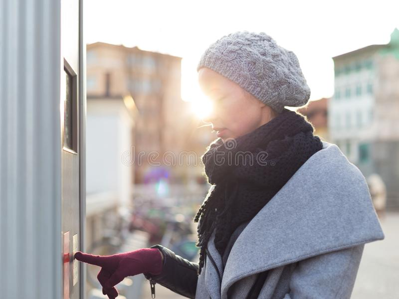 Casual woman buying public transport tickets on city urban vedning machine on cold winter day. royalty free stock photos