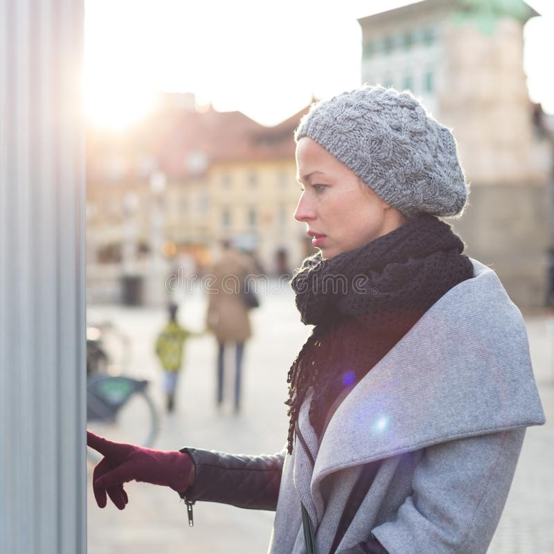 Casual woman buying public transport tickets on city urban vedning machine on cold winter day. royalty free stock photo