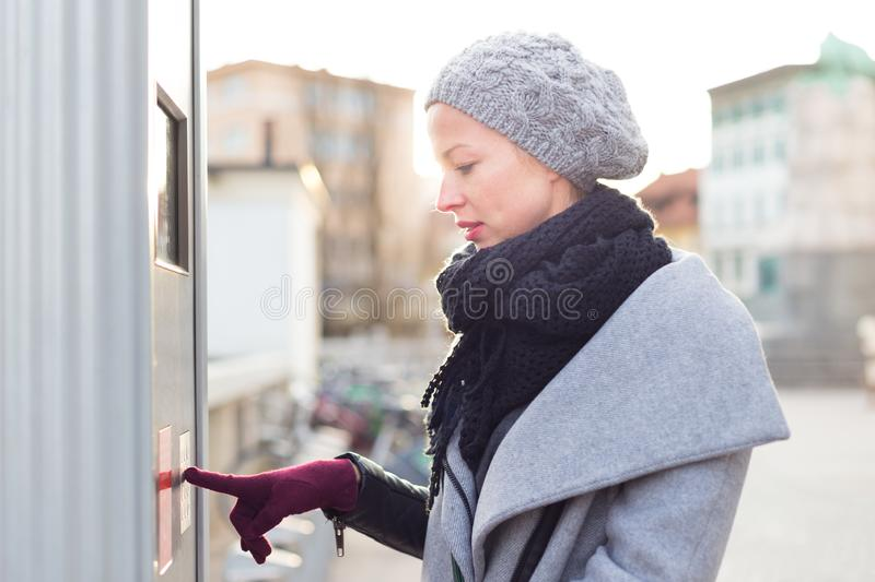 Casual woman buying public transport tickets on city urban vedning machine on cold winter day. royalty free stock images
