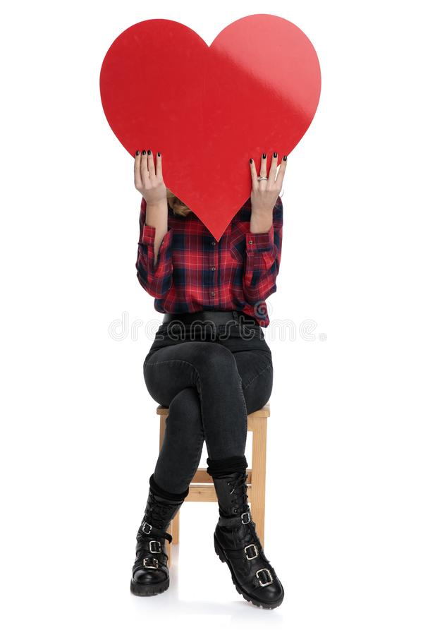 Casual woman sitting with face covered by a heart stock photography