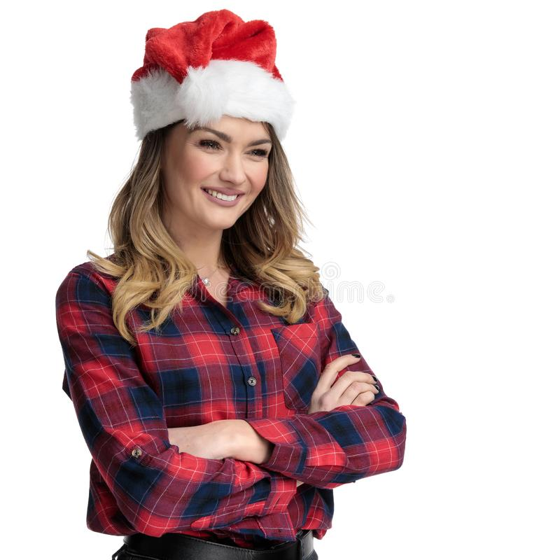 Casual woman with Christmas hat and arms crossed looking away stock images