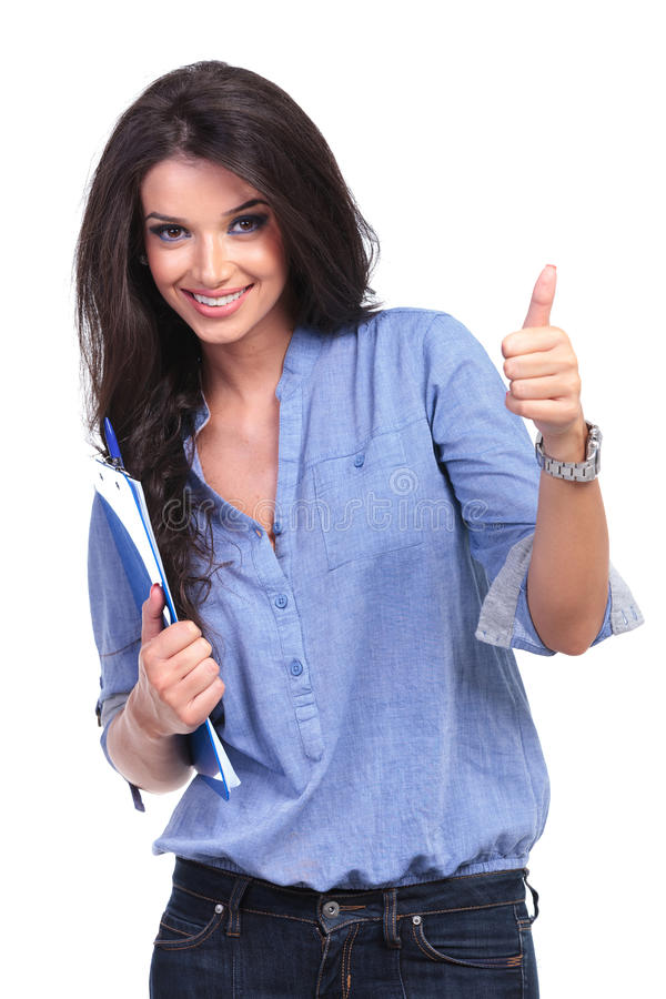 Casual woman with clipboard and thumb up. Young casual woman holding a clipboard and showing the thumb up gesture while smiling. on white background royalty free stock photo