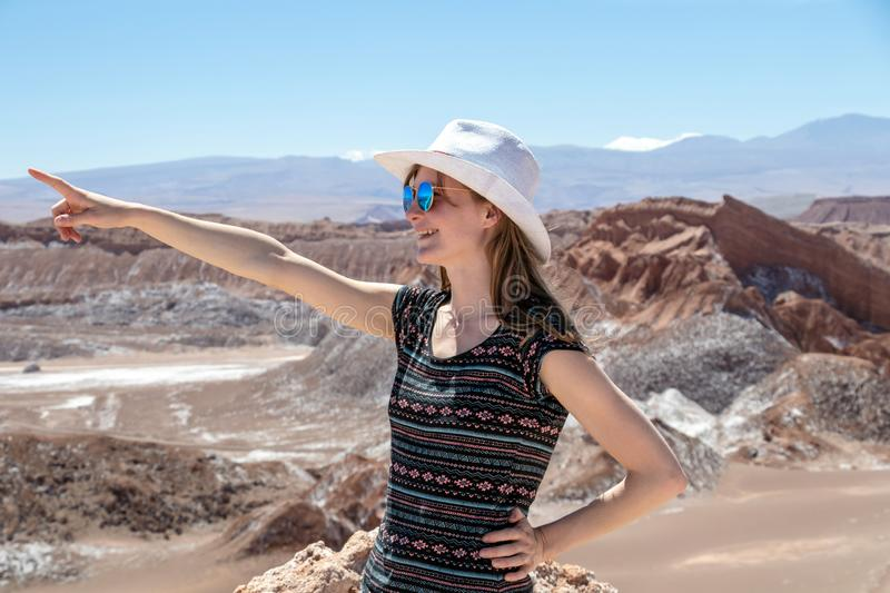 Casual woman enjoy solo trip and admire unique epic landscape of the Moon Valley, Chile. Caucasian blond woman enjoy solo trip and admire unique epic landscape stock images