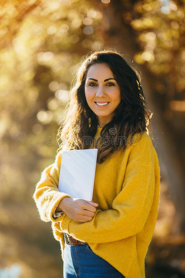 Casual woman holding a book in autumn at the park royalty free stock photo