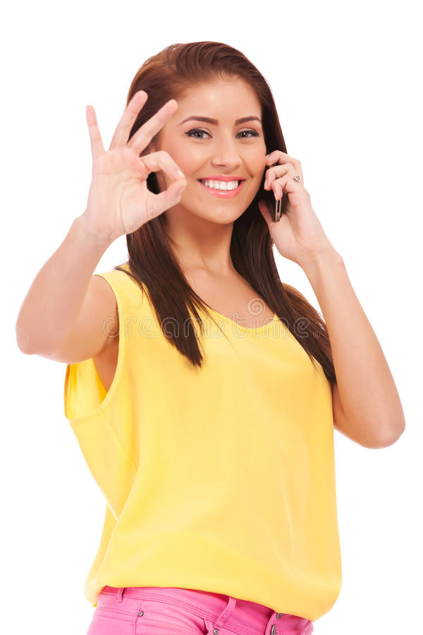 Casual woman with phone and ok gesture. Happy casual woman with phone and ok gesture, isolated royalty free stock images