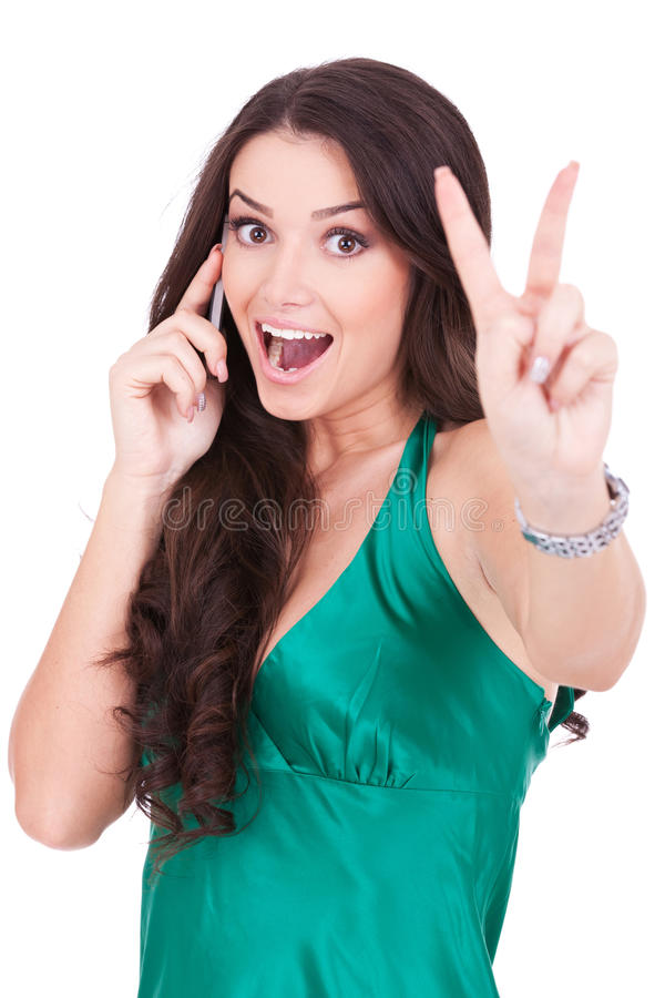 Casual woman with phone and victory gesture. Happy casual woman with phone and victory gesture, isolated royalty free stock photography
