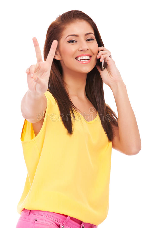 Casual woman with phone and victory gesture. Happy casual woman with phone and victory gesture, isolated on white background stock photo