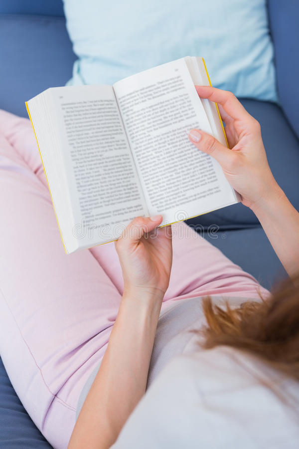 Casual woman reading book on couch royalty free stock photos