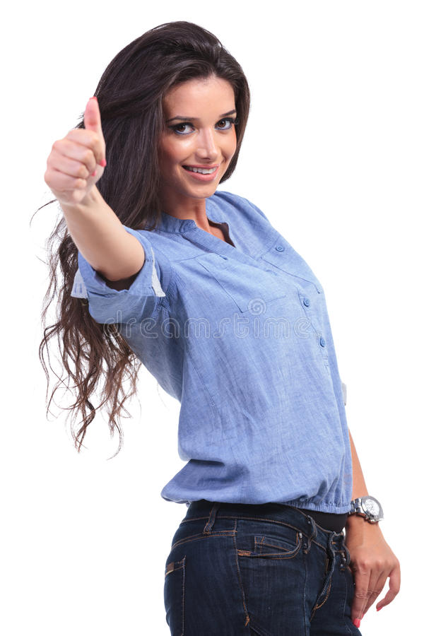 Casual woman shows thumbs up. Side view of a young casual woman showing the thumb up sign to the camera with a smile on her face. on white background royalty free stock photo