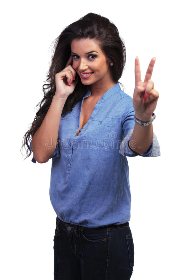 Casual woman shows victory sign while on the phone. Young casual woman showing the victory gesture while speaking on the phone. on white background stock photo