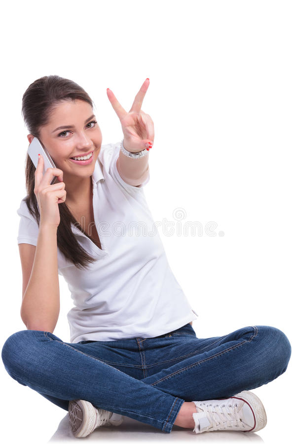 Casual woman sits & victory on phone. Casual young woman sitting with legs crossed and speaking on the phone while showing the victory sign. isolated on white stock image