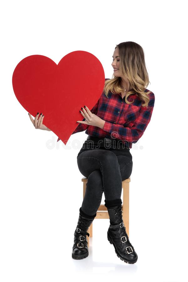 Casual woman sitting with a big heart on hands sideways royalty free stock images