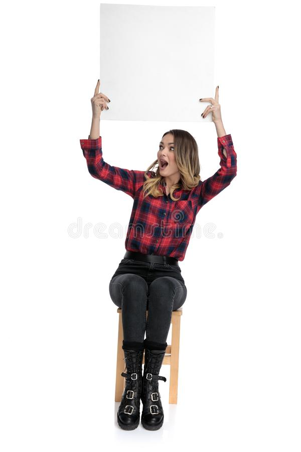 Casual woman sitting with billboard overhead to a side astonished royalty free stock photos