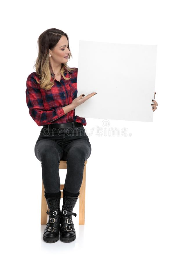 Casual woman sitting with blank billboard to a side stock photography