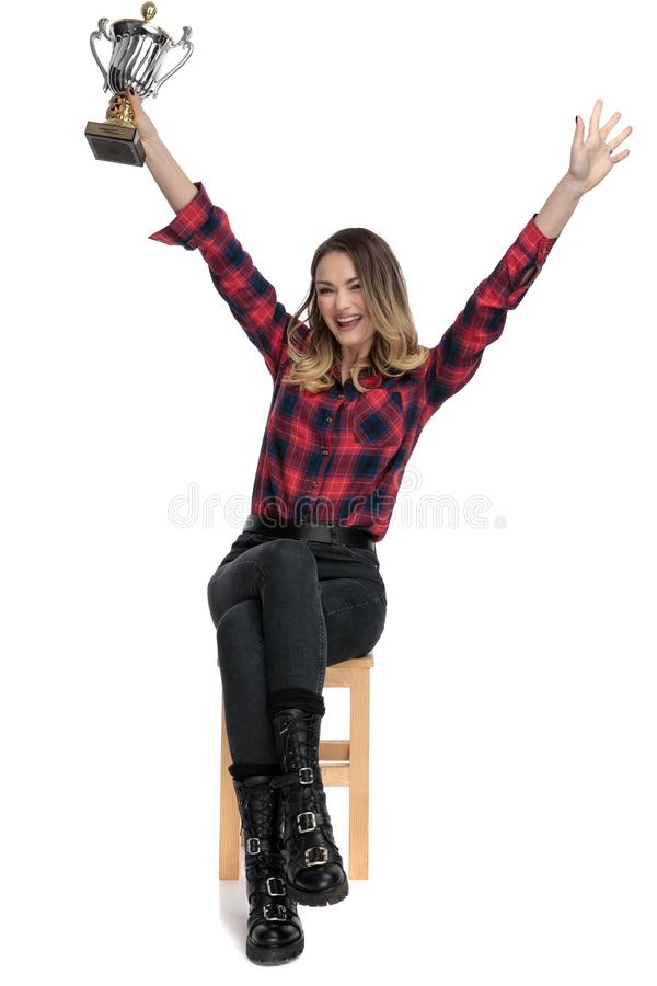 Casual woman sitting with hands in air and trophy stock photography
