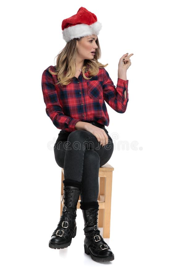 Casual woman sitting and pointing to a side stock image