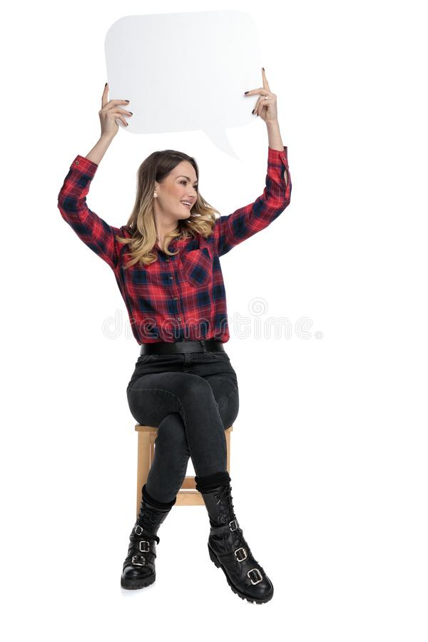 Casual woman sitting with speech bubble overhead and looking sideways royalty free stock image