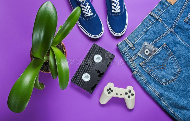 Casual women's retro style denim skirt, video cassette, gamepad. Sneakers shoes, pot with a green plant on purple background. Pop culture, Minimalism stock images