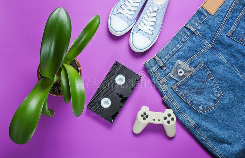 Casual women's retro style denim skirt, video cassette, gamepad, sneakers shoes, pot with. A green plant on purple background. Pop culture, Minimalism royalty free stock photo