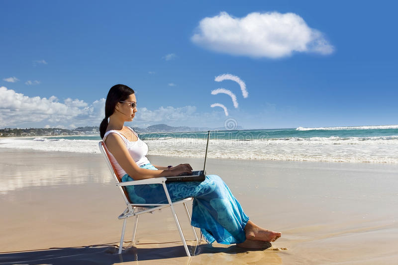 Casual Worker works with laptop at beach royalty free stock image