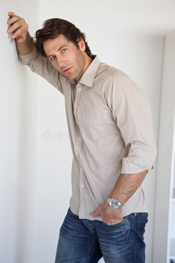 Casual worried businessman leaning on wall royalty free stock photography