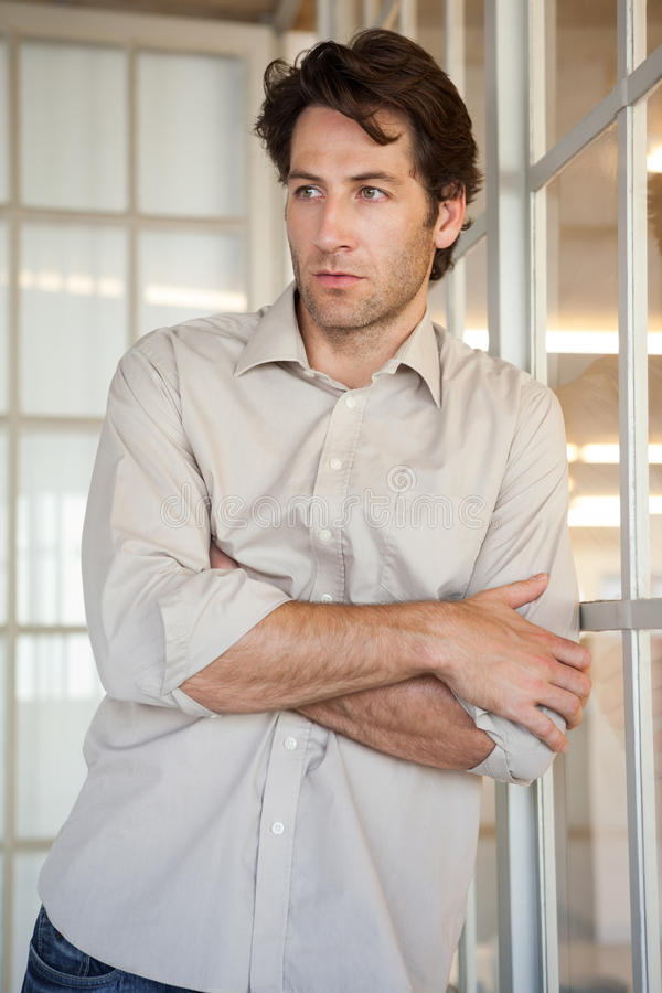 Casual worried businessman leaning on window royalty free stock photo