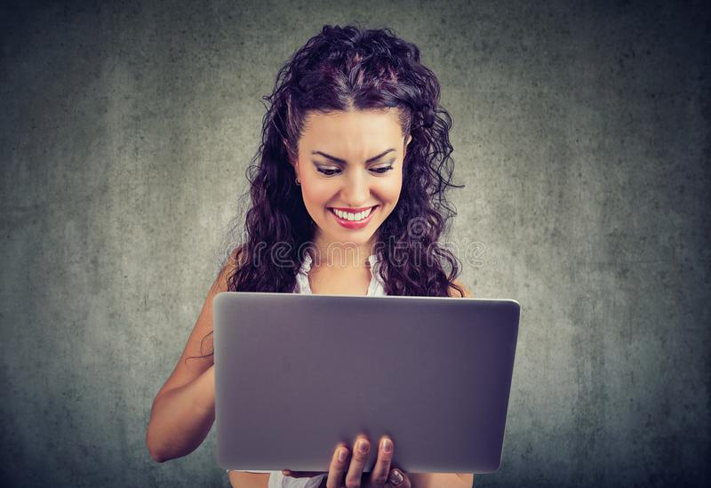Cheerful young woman holding and using laptop royalty free stock image