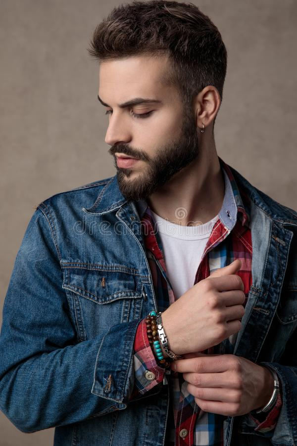 Casual young fashion man wearing blue denim jacket. Adjusting bracelets and looking down side, on brown background in studio royalty free stock photos