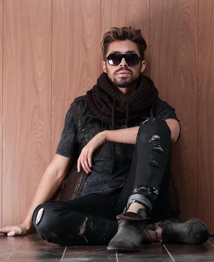 Casual young man with beard sitting on the floor stock image