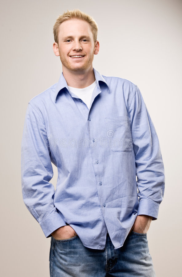 Casual young man with hands in pockets stock photo