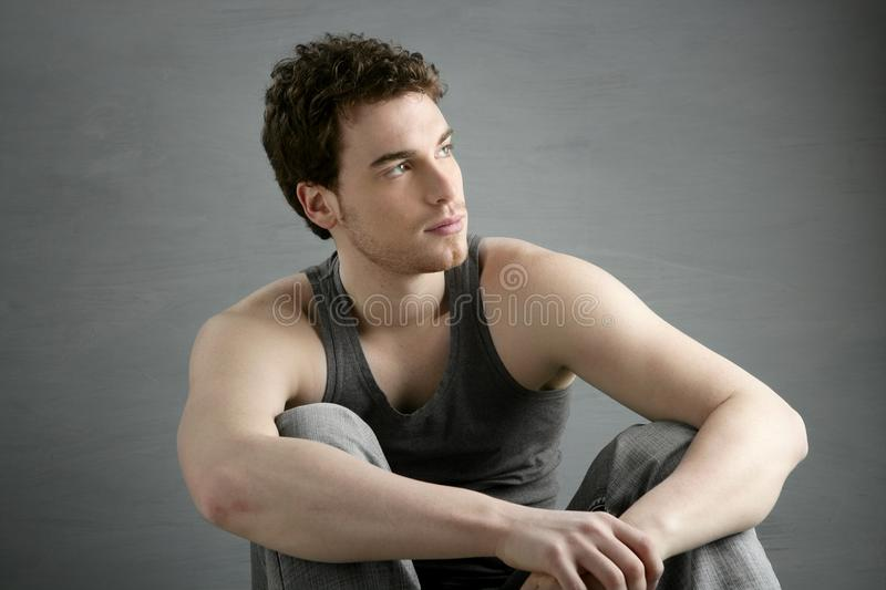 Casual young man portrait sit over gray royalty free stock image