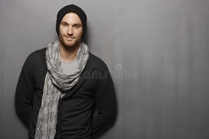 Casual young man smiling over grey wall stock photo