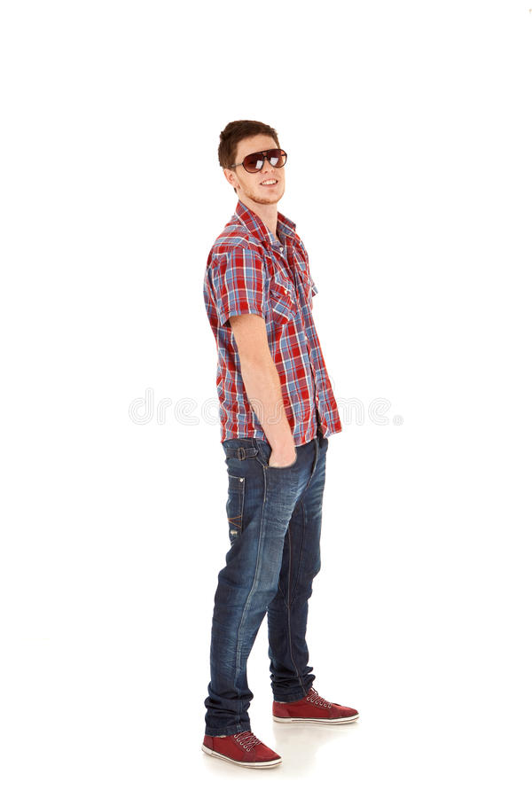 Casual young man standing with hands in pockets stock image