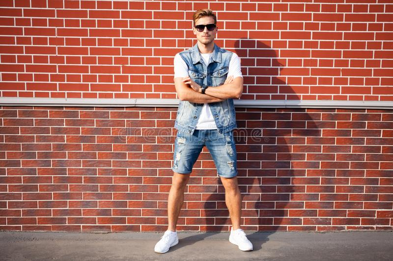 Casual young man stands with his back against a brick wall. royalty free stock photos
