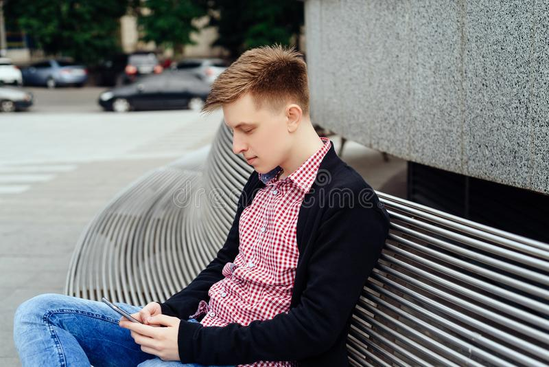 Casual young man using smart phone sitting on bench in city. stock photography